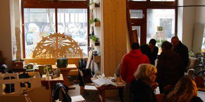 Ein Café mit vielen hellen Holzelementen in dem mehrere Menschen an verschiedenen Tischen sitzen und stehen