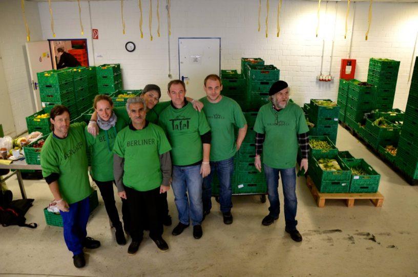 Sieben Personen in grünen T-Shirts bei der Berliner Tafel mit grünen Kisten voller Lebensmitteln hinter ihnen