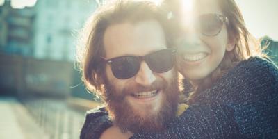 Ein lachendes Paar mit Sonnenbrillen im Sonnenschein