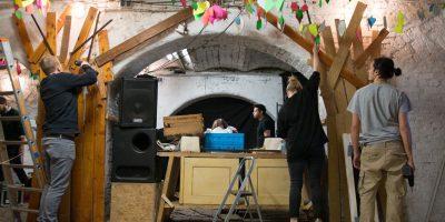Menschen beim Dekorieren und Aufbauen von Girlanden in einem alten Gebäude