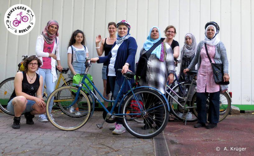 Mehrere Frauen stehen beisammen, einige mit Fahrrädern und Helmen, oben links im Bild das Logo der Organisation Bikeygees