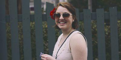 lachendes Mädchen mit Sonnenbrille und Blume im Haar
