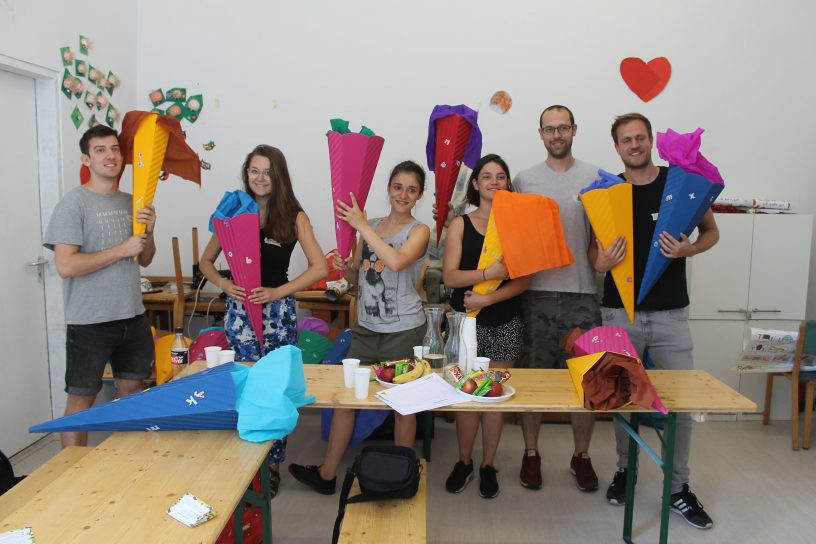 Six people posing with their colourful handicrafted candy cones
