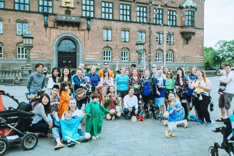 Many people with children in front of a castle with soap bubbles