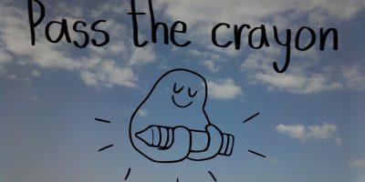 Das Maskotchen von der Organisation Pass the Crayon hält einen Wachsmaler, darüber der schwarze Schriftzug PASS THE CRAYON, im Hintergrund sieht man blauen Himmel mit wenigen Wolken