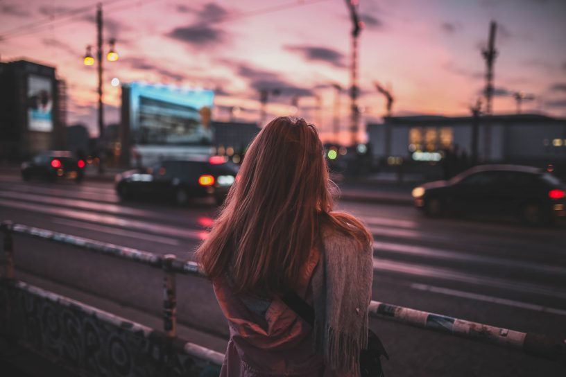 woman from the back in front of a street during sunset