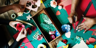 hands cutting colourful flowers out of paper