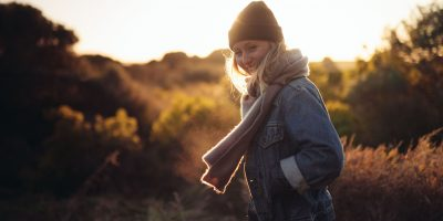 Laughing woman outside with hat and scarf