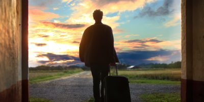 Man with suitcase in front of sunset