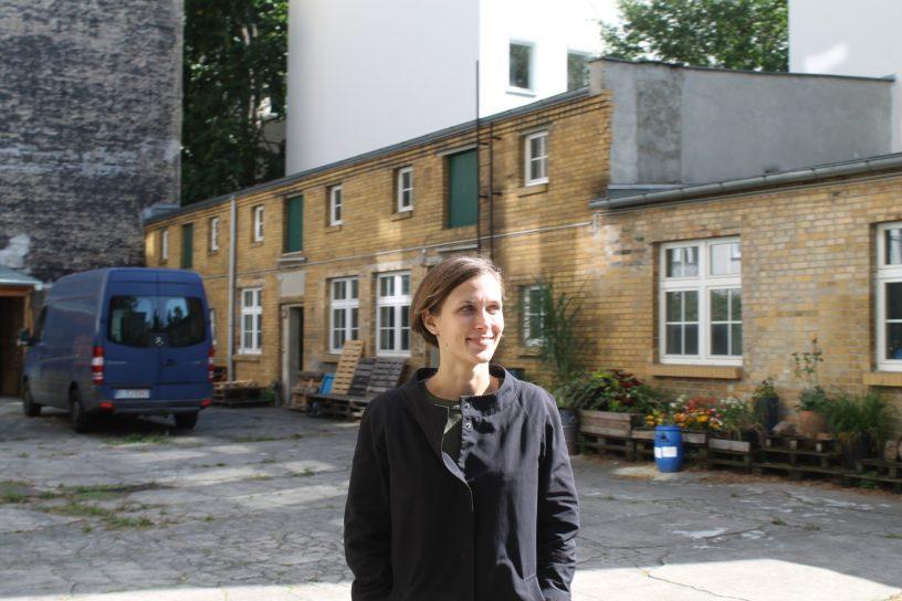 Camille steht in einem Hinterhof