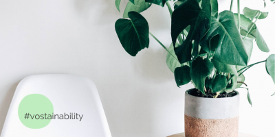Weißer Stuhl mit #vostainability Schriftzug. Daneben eine Pflanze