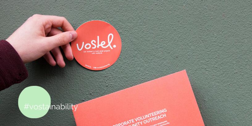 Ein vostel.de Sticker und eine Broschüre vor einer grünen Wand
