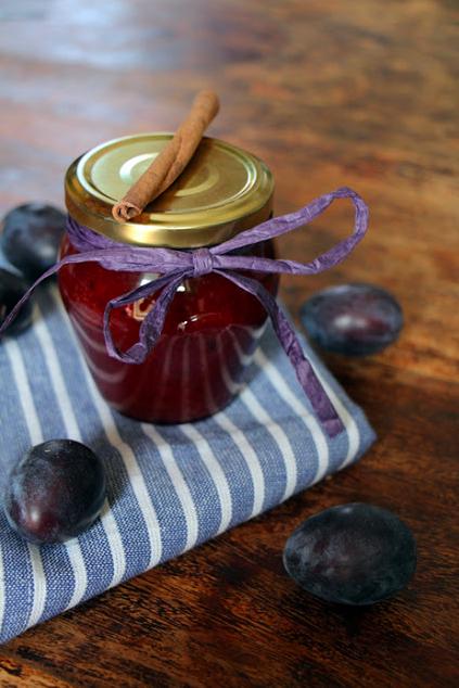 Rote Marmelade im Glas steht als Geschenk verpackt auf einem Tisch. Daneben liegen Zwetschgen.