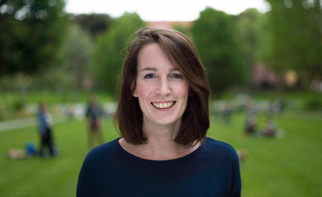Frau mit braunen Haaren und dunkelblauem Oberteil lächelt in die Kamera. Im Hintergrund ist eine verschwommene Wiese.