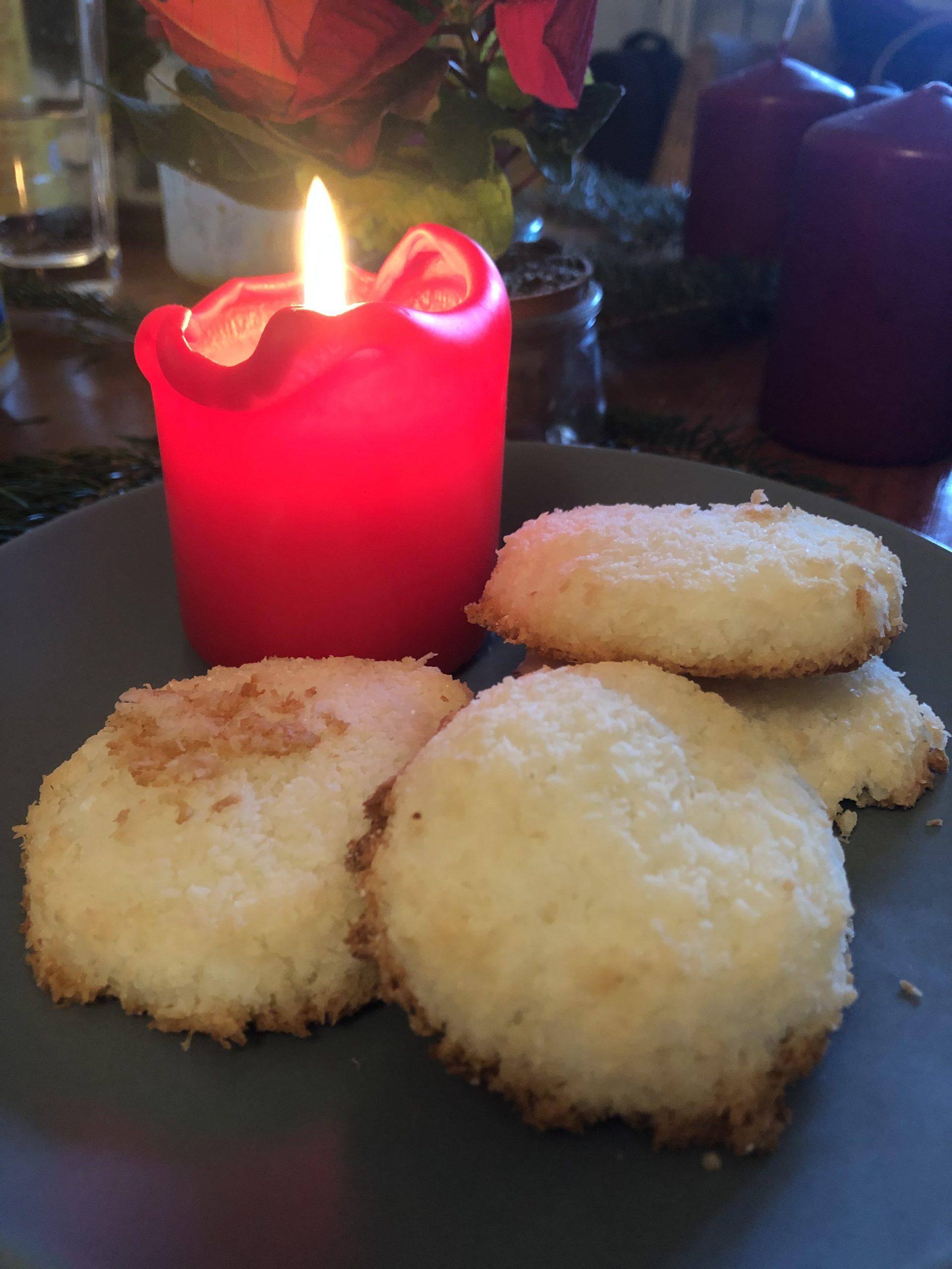 Eine angezündete rote Kerze und 4 weiß braune Kokosmakronen.