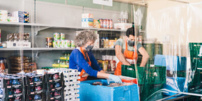 Frau und Mannsortieren Lebensmittel bei der Tafel