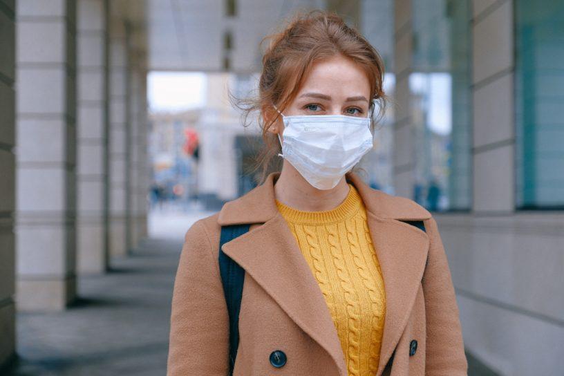 Junge Frau vor Gebäude mit Maske