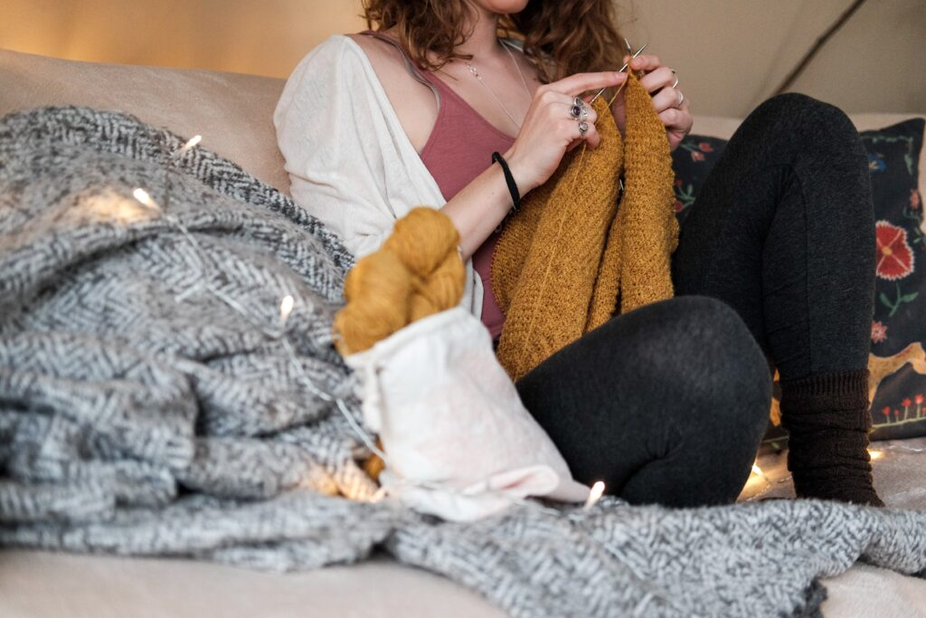 Woman sitting on the sofa in a cosy atmosphere knitting a mustard yellow scarf.