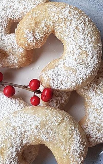 Vanillekipferl mit Puderzucker und rote Beeren an einem Ast.