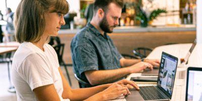 Zwei Personen sitzen an ihren Laptops an einem Tisch, scheinbar arbeitend.