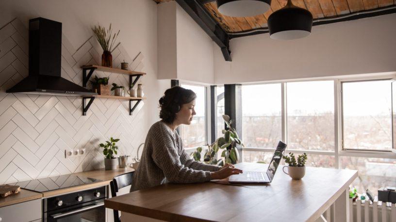 Eine junge Frau in ihrer Küche sitzt am Laptop