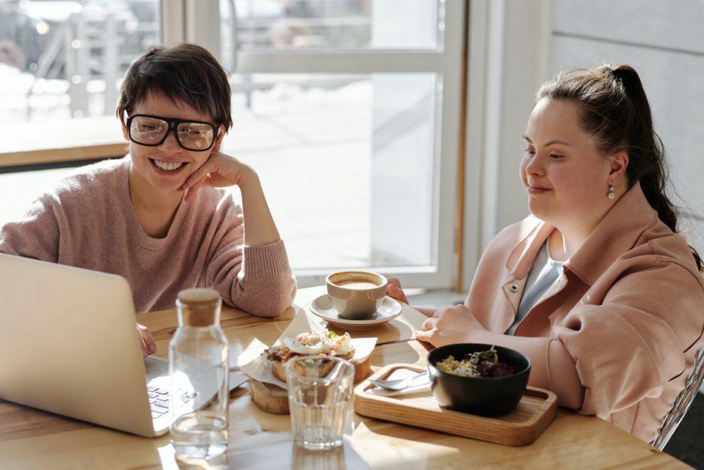 Zwei Frauen sitzen an einem Tisch und schauen auf einen Laptop
