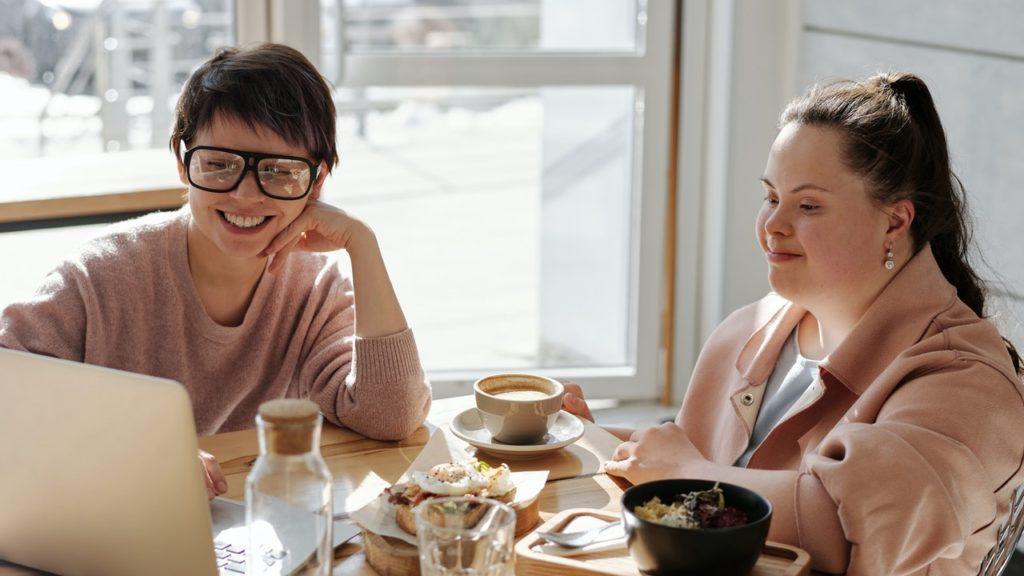 Zwei Frauen sitzen an einem Tisch und schauen auf einen Laptop.