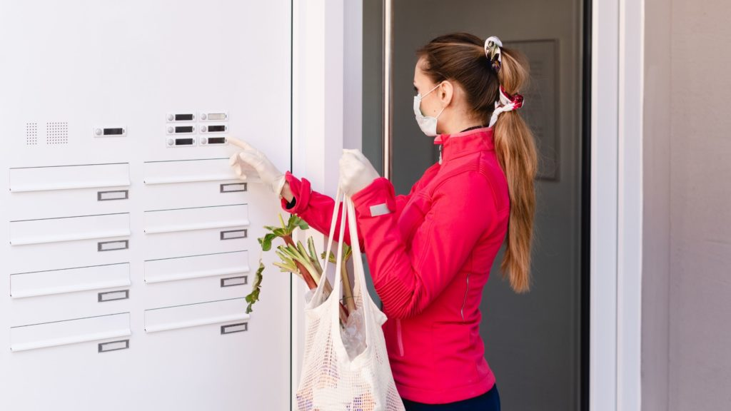 Frau klingelt an Haustür mit Einkaufsbeutel in der Hand