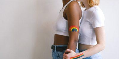 Zwei Frauen stehen nebeinander mit Regebogenfarben auf dem Arm