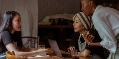 3 Frauen sitzen am Laptop und diskutieren