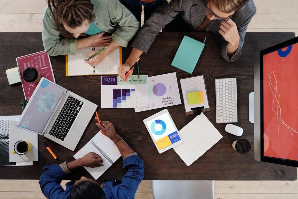 Foto von Oben auf Personen am Tisch mit Unterlagen und Laptop