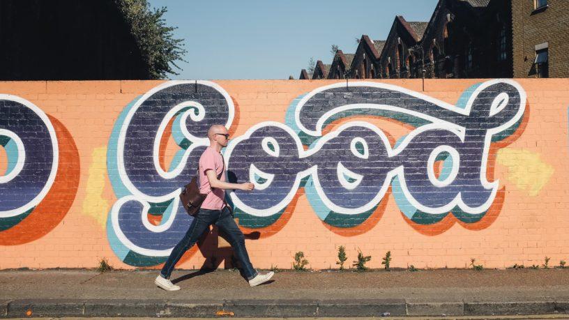Man läft an Wand entlang auf der steht: Good